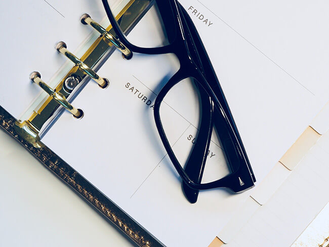 Close up of calendar planner with black glasses on top