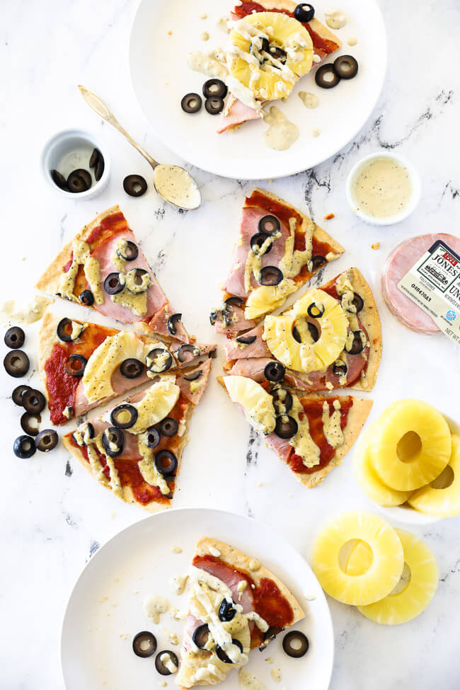 vertical overhead image of hawaiian pizza cut into slices on marble and then served up on two plates with extra dairy free sauce drizzled on top.
