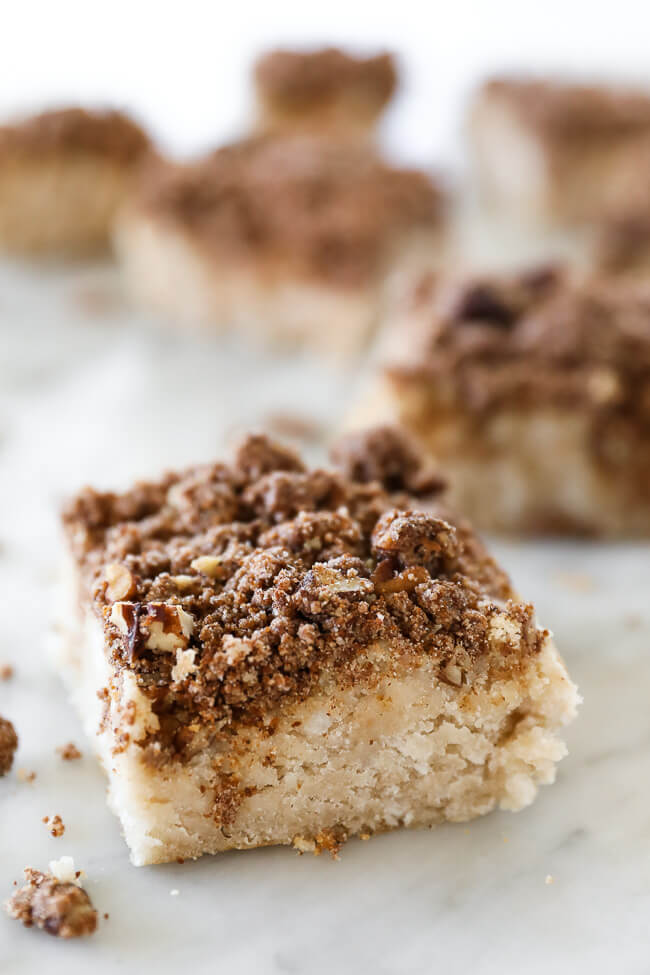 Close up of an angled image of one square of gluten free coffee cake with more squares blurry in the background.