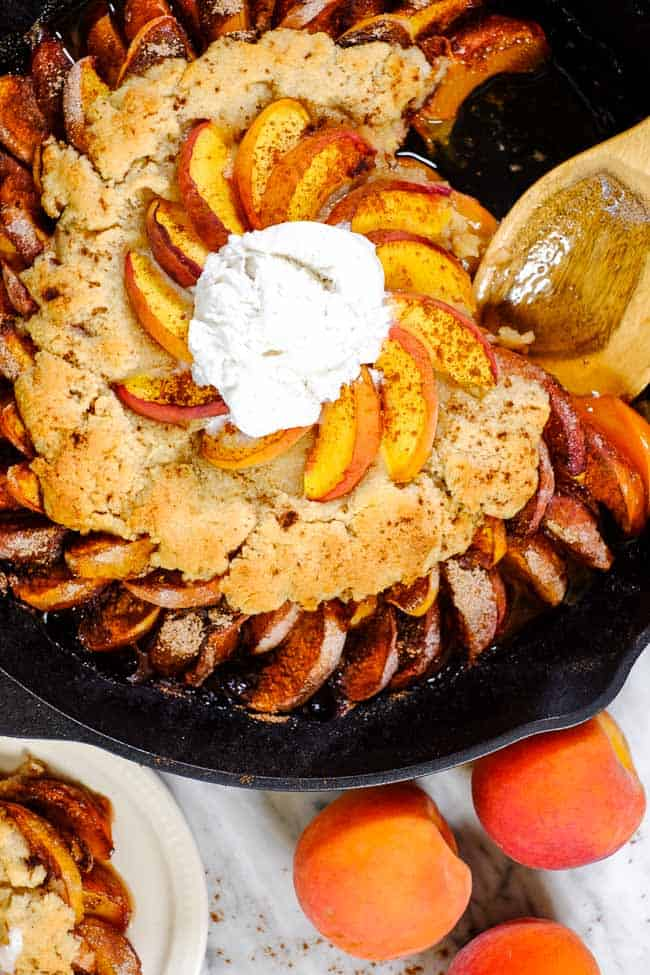 Peach cobbler in cast iron skillet with scoop of ice cream on top