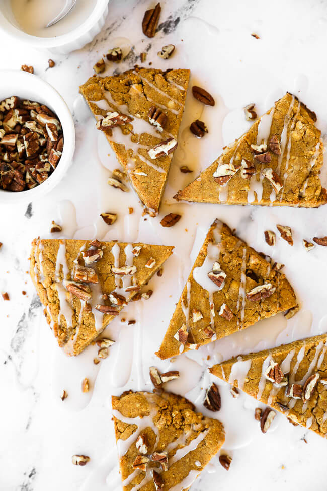 Vertical image of gluten free and vegan pumpkin scones spread out on marble with icing drizzled on top and sprinkled with chopped pecans.