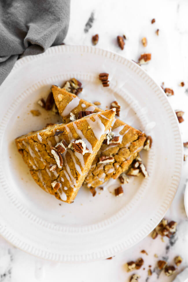 Vertical image of two gluten free and vegan pumpkin scones stacked on a plate with icing and chopped pecans on top.