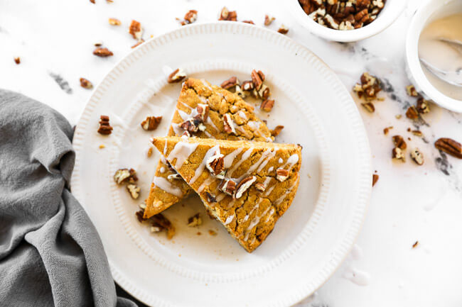 Two gluten free vegan pumpkin scones on a plate with chopped pecans and icing on top.