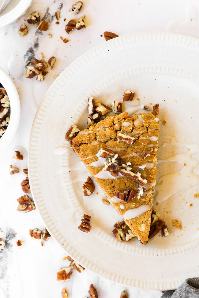 Vertical image of one pumpkin scone on a plate with icing drizzled on top and sprinkled with chopped pecans.