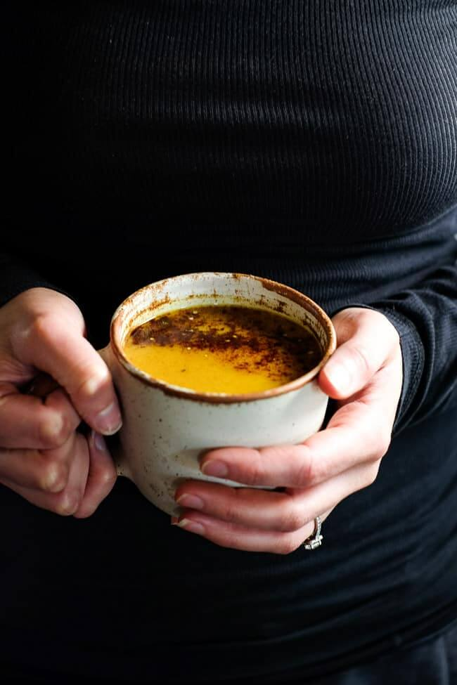 Holding a mug of golden milk latte. It's topped with cinnamon and hemp seeds.