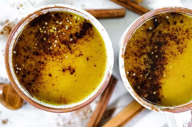 Golden milk latte is two mugs with cinnamon and hemp seeds sprinkled on top.