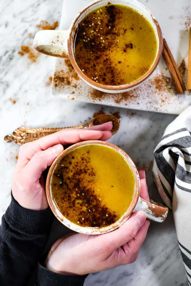 Golden milk latte in two mugs, holding onto one of the mugs. They're topped with cinnamon and hemp seeds.