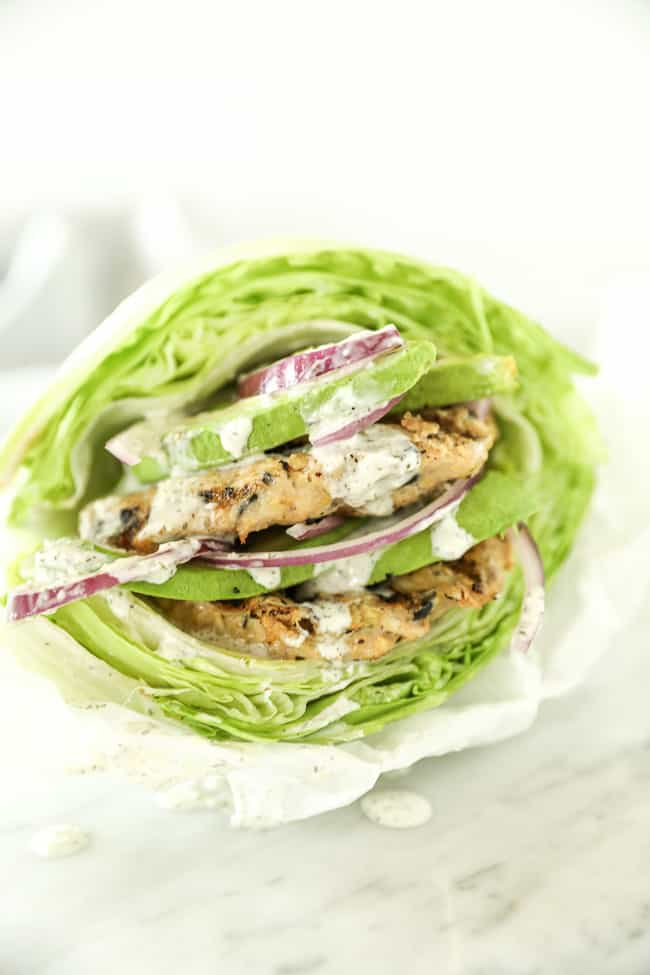 Two Greek turkey burgers stacked between lettuce buns. Topped with avocado and red onion and drizzled with tzatziki sauce.