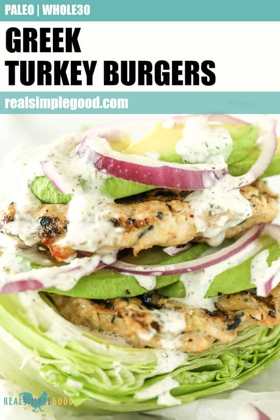 Close up image of Greek turkey burgers on top of lettuce with tzatziki sauce dripping down the sides. Toppings include avocado and red onion. Text overlay at top of image for pinterest.