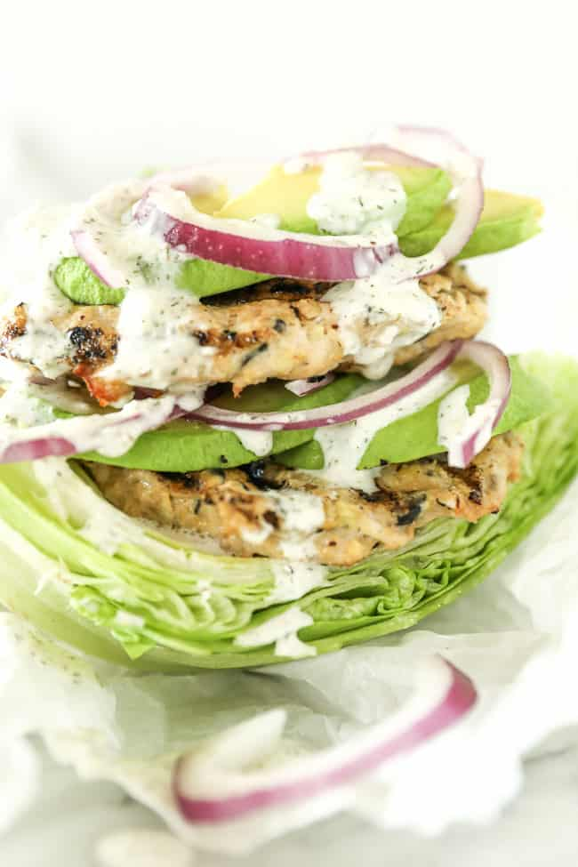 Close up of turkey burgers stacked on lettuce with avocado, red onion and tzatziki sauce.