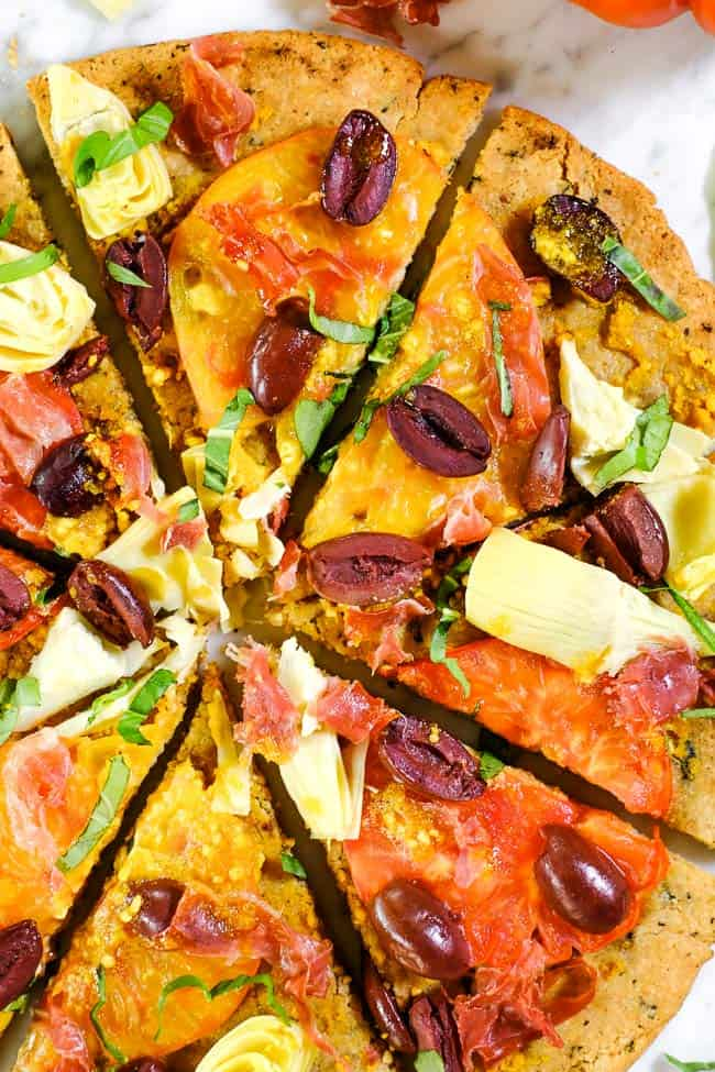 Close up grilled paleo pizza with heirloom tomatoes, artichoke hearts, kalamata olives, prosciutto and fresh basil.