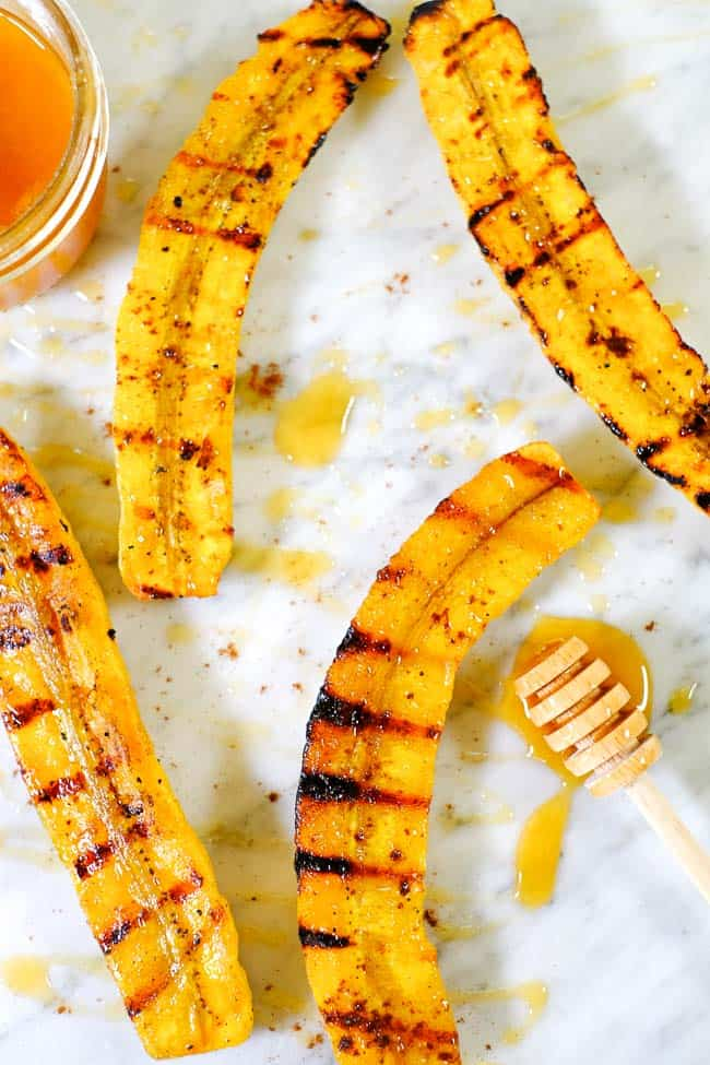 Grilled plantains spread out on marble with honey and cinnamon.