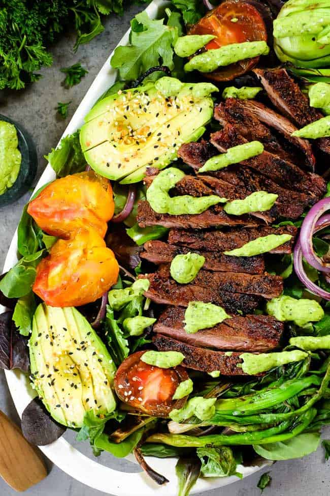 Grilled steak salad on a plate with avocado, tomatoes and green sauce