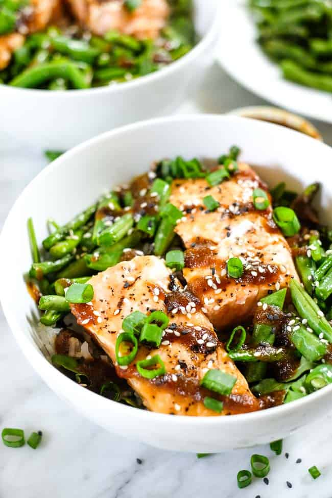 Grilled salmon over greens in a bowl with sauce on top