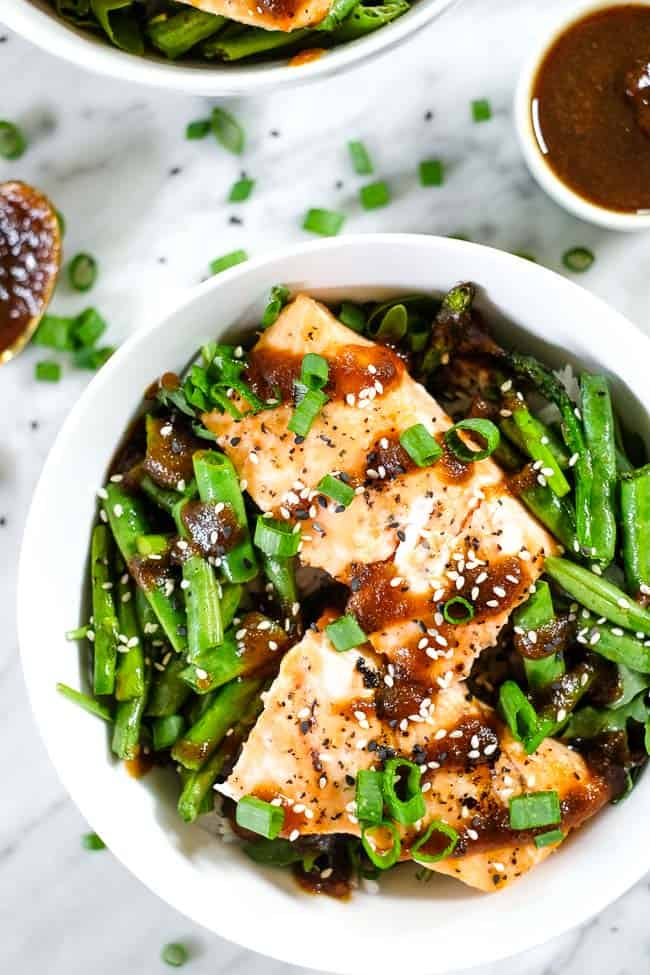 Grilled teriyaki salmon in a bowl with green beans, asparagus, rice and greens. Topped with teriyaki sauce, green onion and sesame seeds.