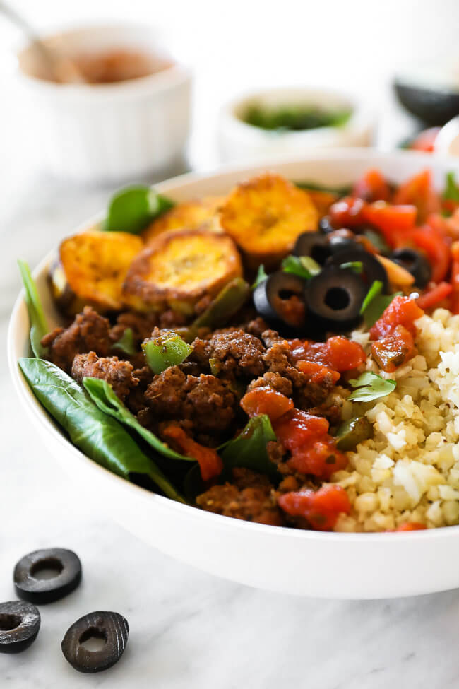ground beef taco bowl with greens, plantains and cauli rice close up angle image