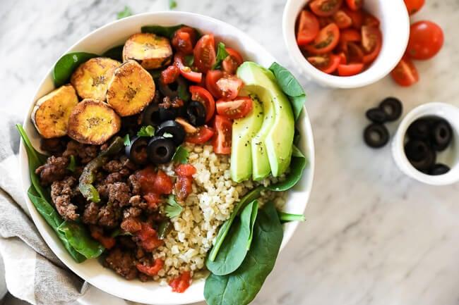 ground beef taco bowl with greens, plantains and cauli rice horizontal image