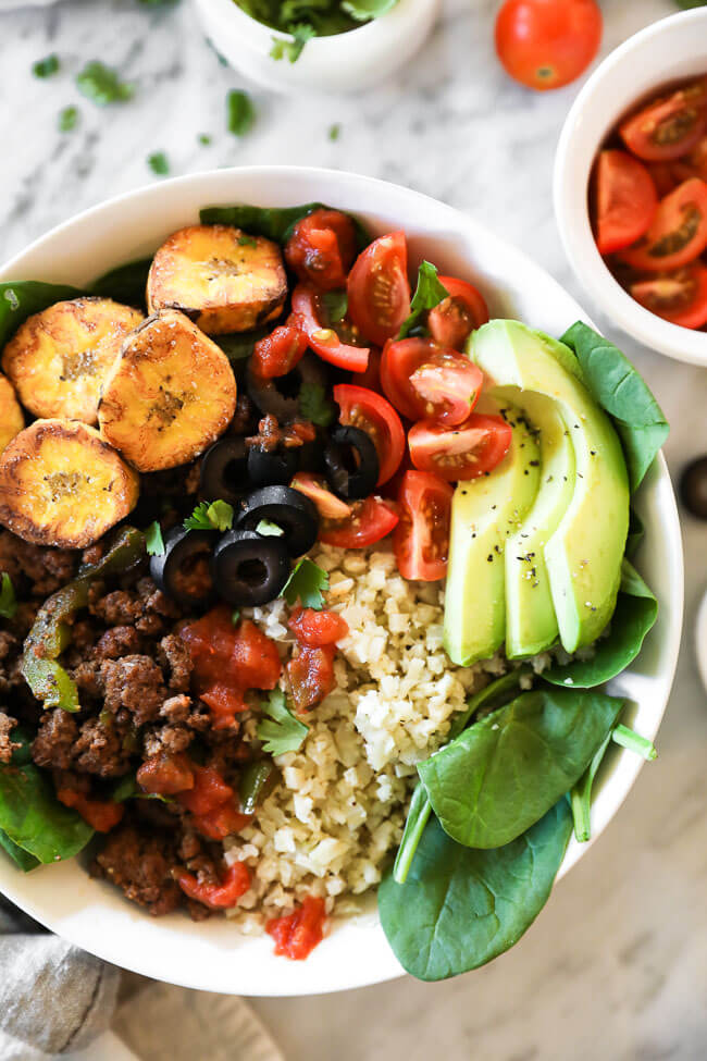 ground beef taco bowl with greens, plantains and cauli rice close up vertical image