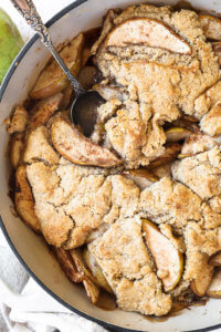 Vertical overhead close up image of pear cobbler in a skillet with a serving spoon dug in.