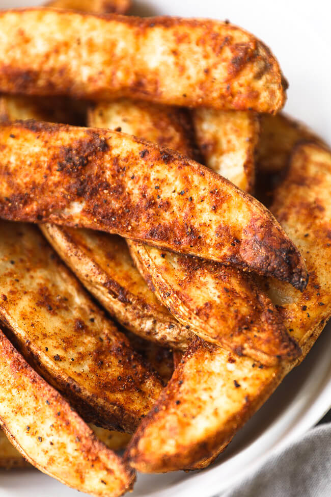 Close up angled image of crispy air fryer potato wedges in a bowl.