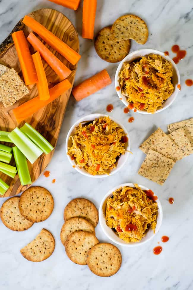 Healthy buffalo chicken dip in ramekins with hot sauce, crackers, carrots and celery.