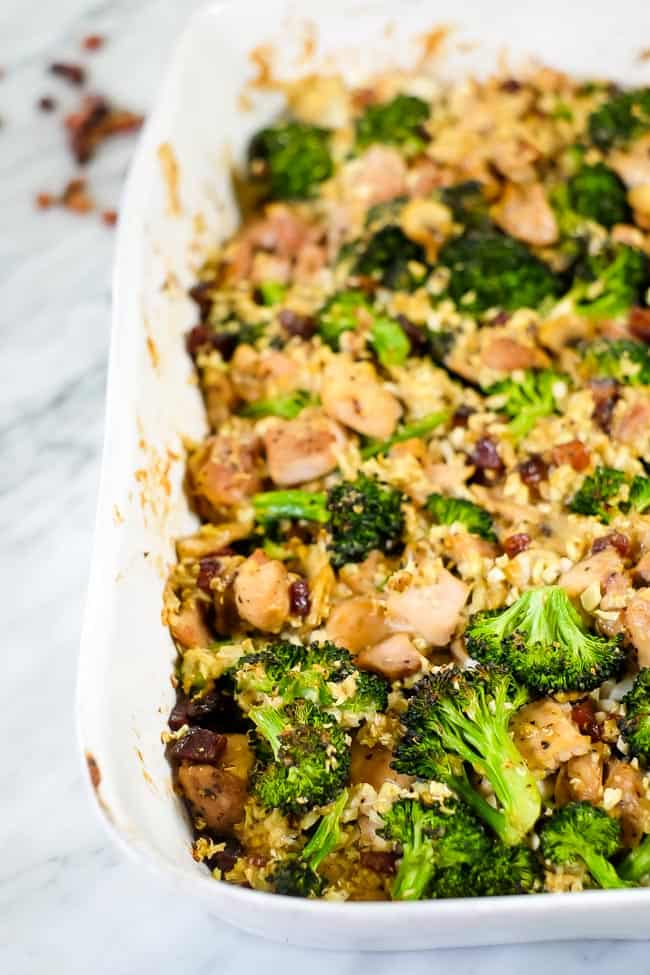 Healthy chicken and broccoli casserole with bacon and cauliflower rice in a creamy sauce in a casserole dish.