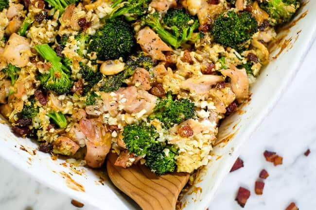 Close up of this healthy chicken and broccoli casserole with bacon and cauliflower rice in a creamy sauce in a casserole dish with a serving spoon.