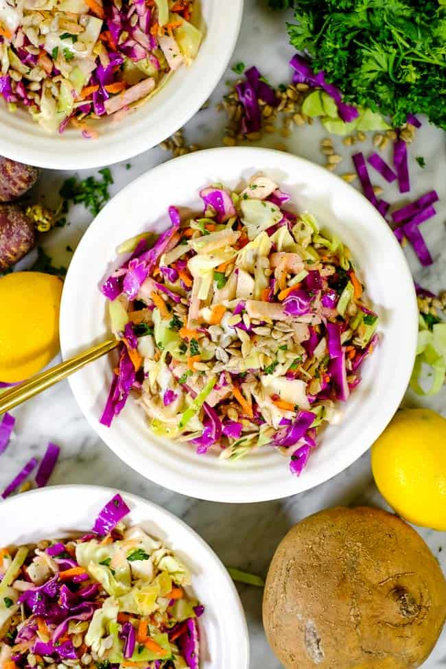 Healthy coleslaw in three bowls with ingredients used in salad scattered around on the table.