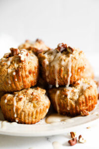 Gluten free and vegan banana muffins stacked on a plate with maple glaze drizzled on top and sprinkled with chopped pecans.