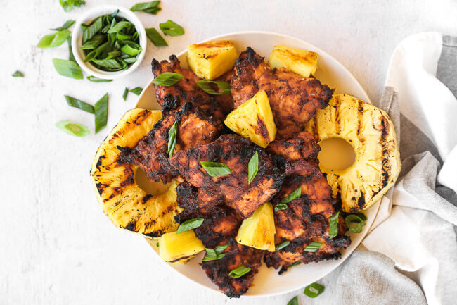 Grilled chicken and pineapple on a plate with chopped green onion sprinkled on top.