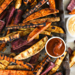 Vertical overhead image of grilled sweet potato fries on a grilling pan with ketchup and chipotle aioli on the side.