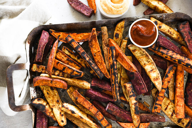 Horizontal overhead image of grilled sweet potato fries on a grilling pan with ketchup and chipotle aioli on the side.
