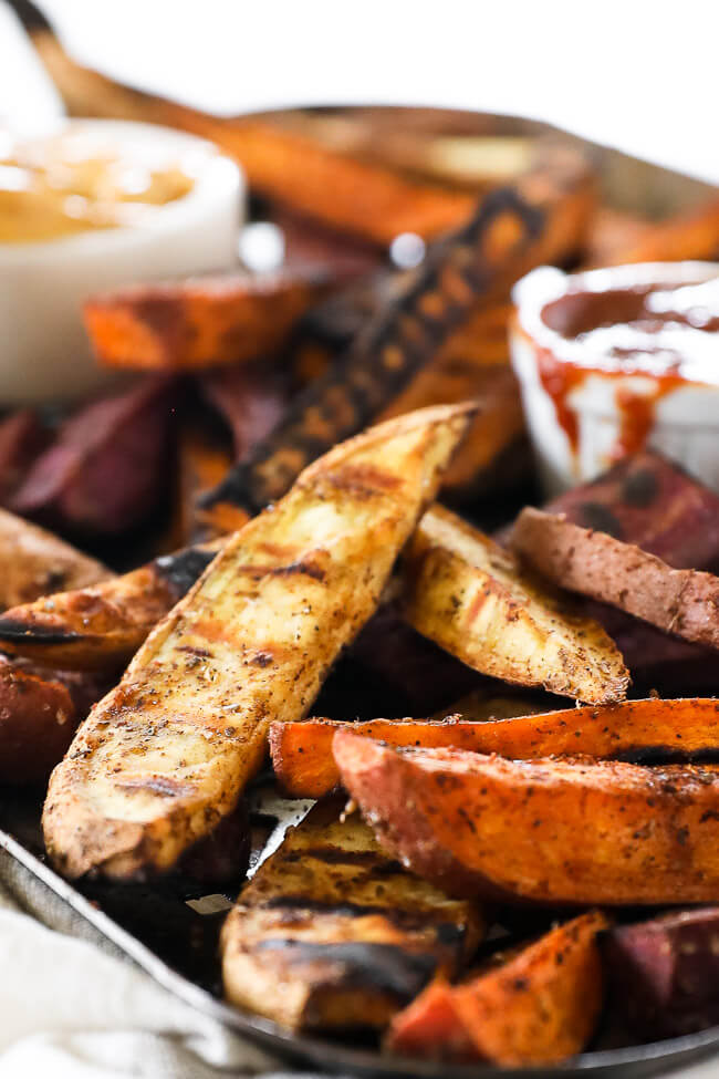 Vertical angled close up image of grilled sweet potato fries on a grilling pan.