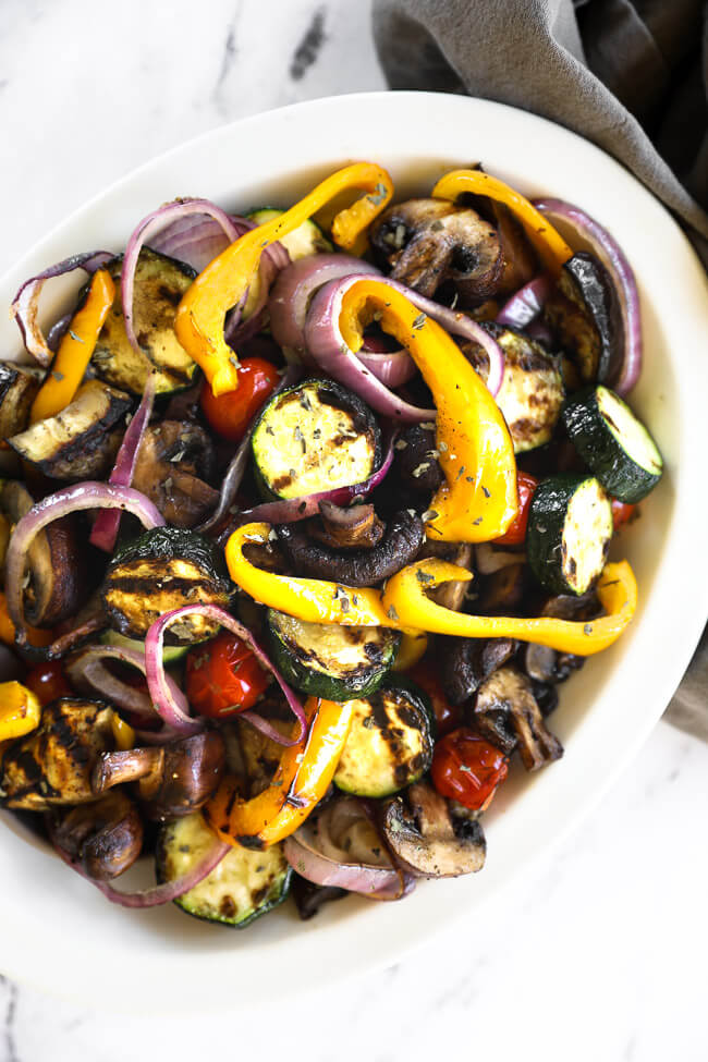 Close up overhead shot of oval bowl filled with grilled vegetables
