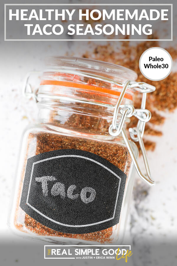 Homemade taco seasoning in a jar laying on the counter with text at top