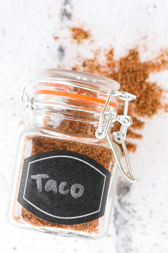 Homemade taco seasoning in a jar laying on the counter