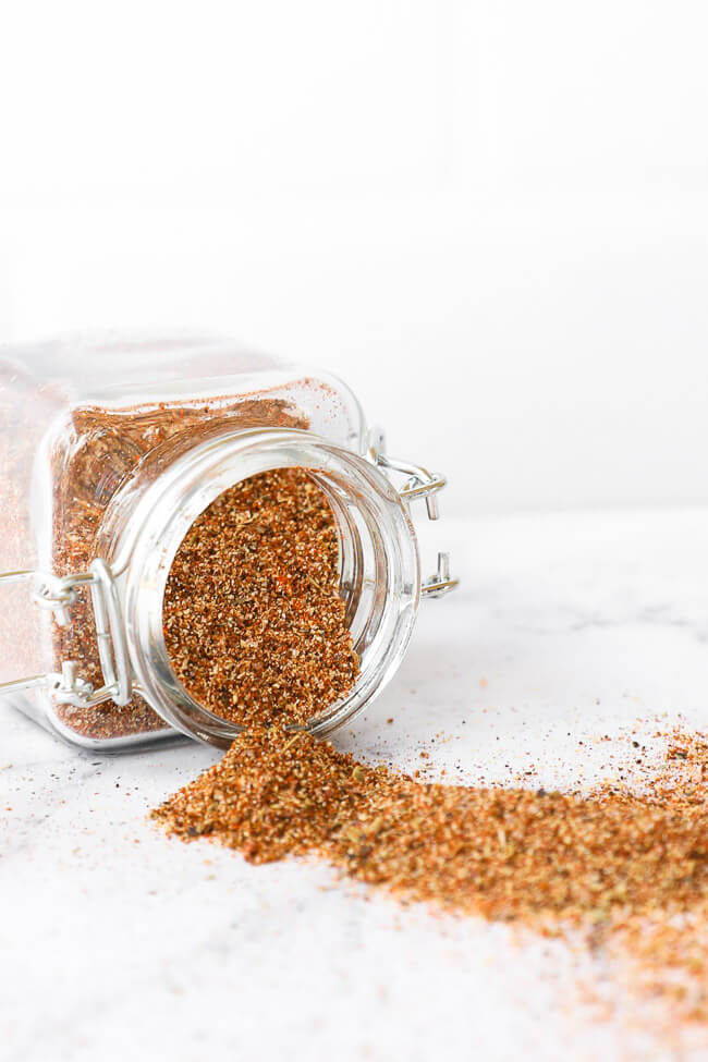 Homemade taco seasoning in a jar tipped over on side with seasoning spilling out