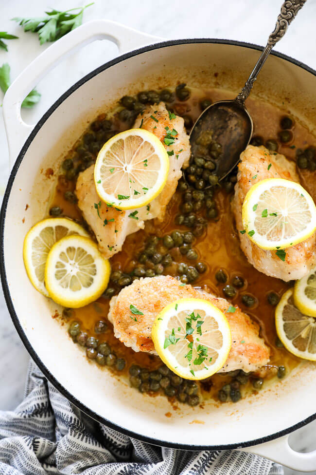 Vertical overhead image of healthy lemon chicken piccata in a large skillet with sauce, capers, lemon rounds and chopped parsley. Serving spoon in skillet.
