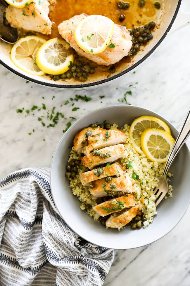 Vertical overhead image of healthy lemon chicken piccata sliced and served in a bowl with lemon rounds and chopped parsley. Fork dug into bowl.