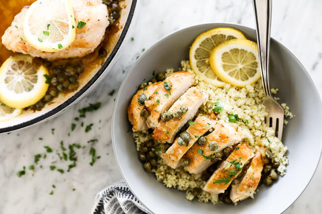 Horizontal overhead image of healthy lemon chicken piccata sliced and served in a bowl with cauliflower rice and lemon rounds. Fork dug into bowl.
