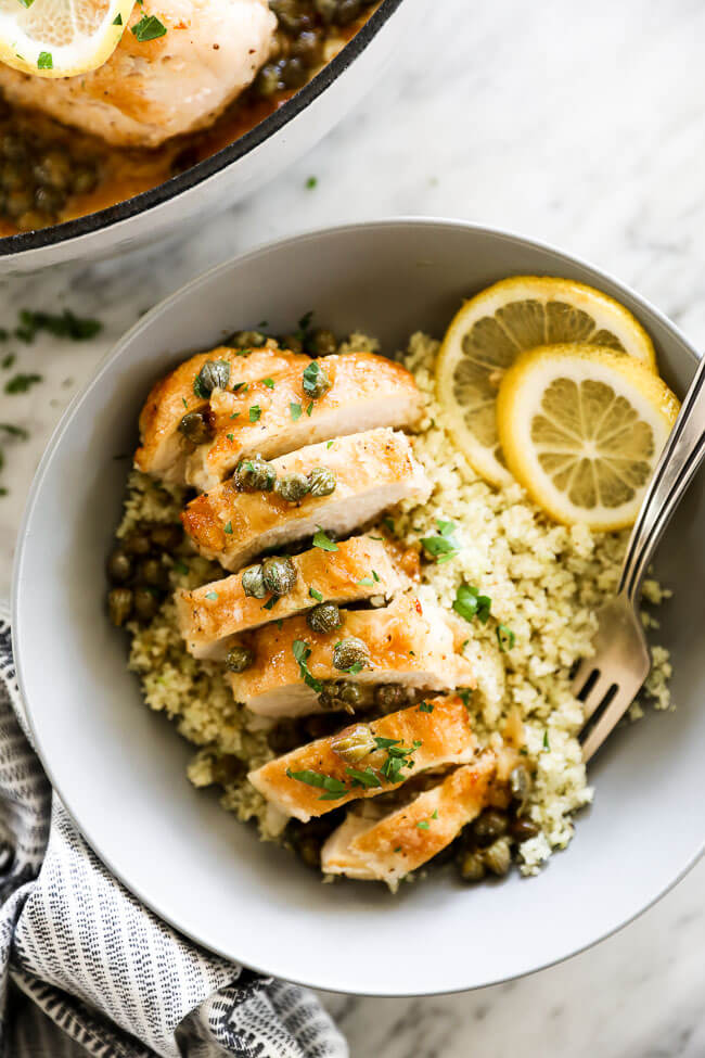 Vertical overhead close up image of healthy lemon chicken piccata in a bowl served over cauliflower rice with lemon rounds and chopped parsley. Fork dug into bowl.