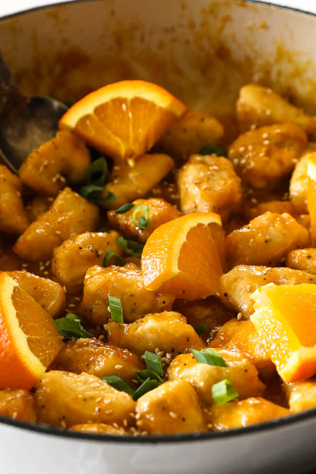 Healthy orange chicken in pan with orange slices close up vertical image