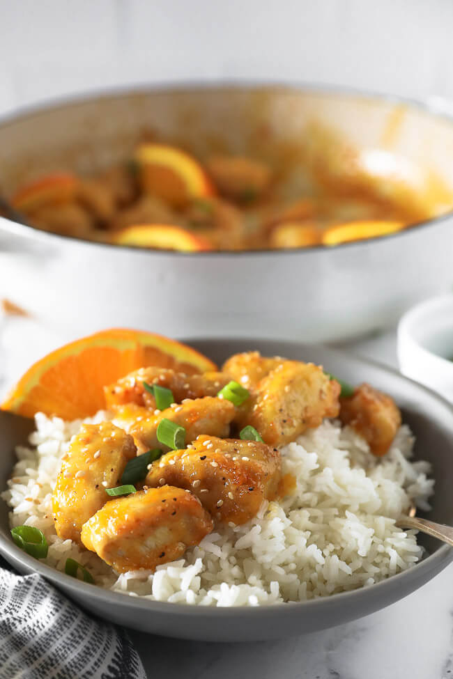 Healthy orange chicken in a bowl over rice angled vertical image