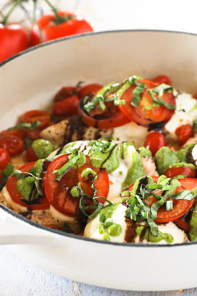 Vertical angled image of chicken caprese in skillet. Chicken breasts topped with mozzarella cheese, tomatoes, pesto, balsamic and fresh basil.