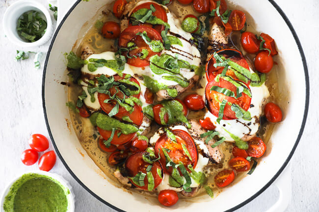 Horizontal overhead image of chicken caprese in skillet. Chicken breasts topped with mozzarella cheese, tomatoes, pesto, balsamic and fresh basil.