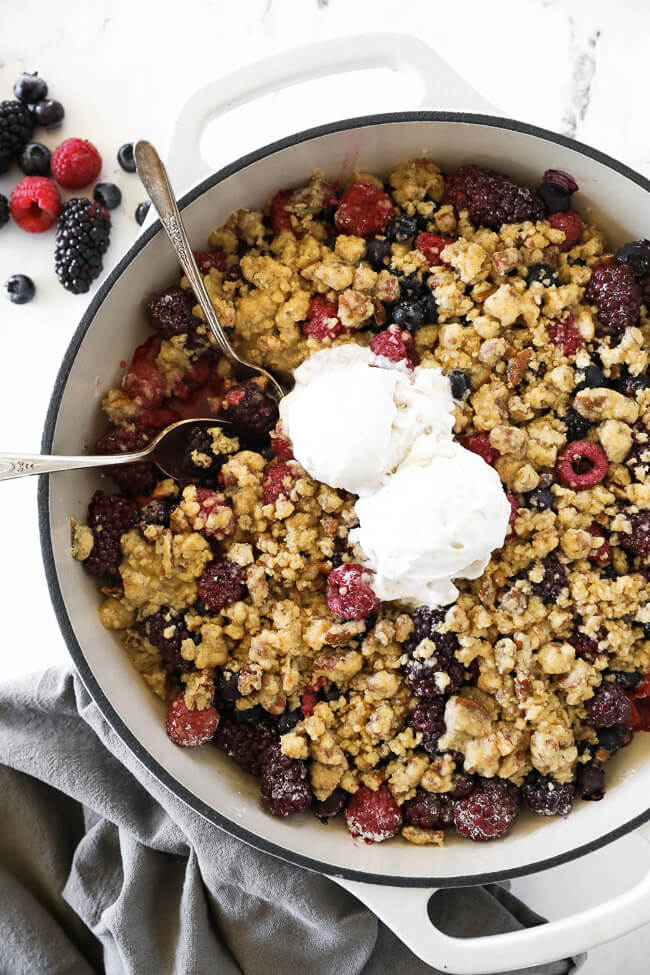Overhead vertical image of mixed berry crisp in skillet with two spoons dug in and two scoops of ice cream on top.