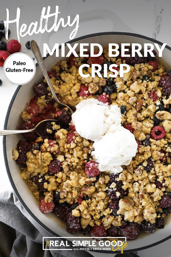 Overhead vertical image of mixed berry crisp in skillet with two spoons dug in and two scoops of ice cream on top. Text overlay at top.