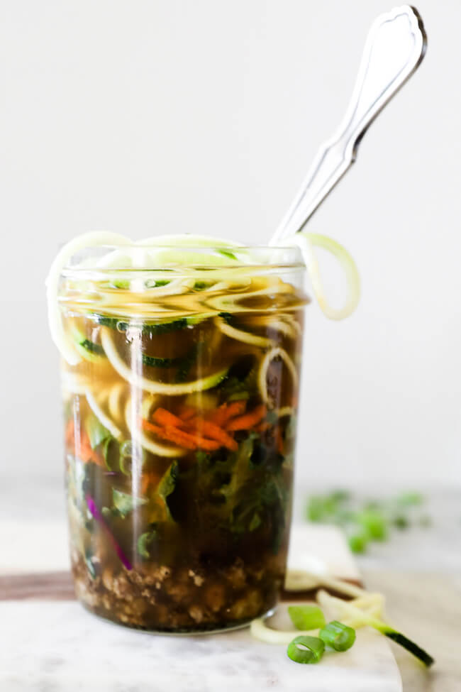 Straight on vertical image of healthy ramen noodles in a jar with broth poured in and a spoon.