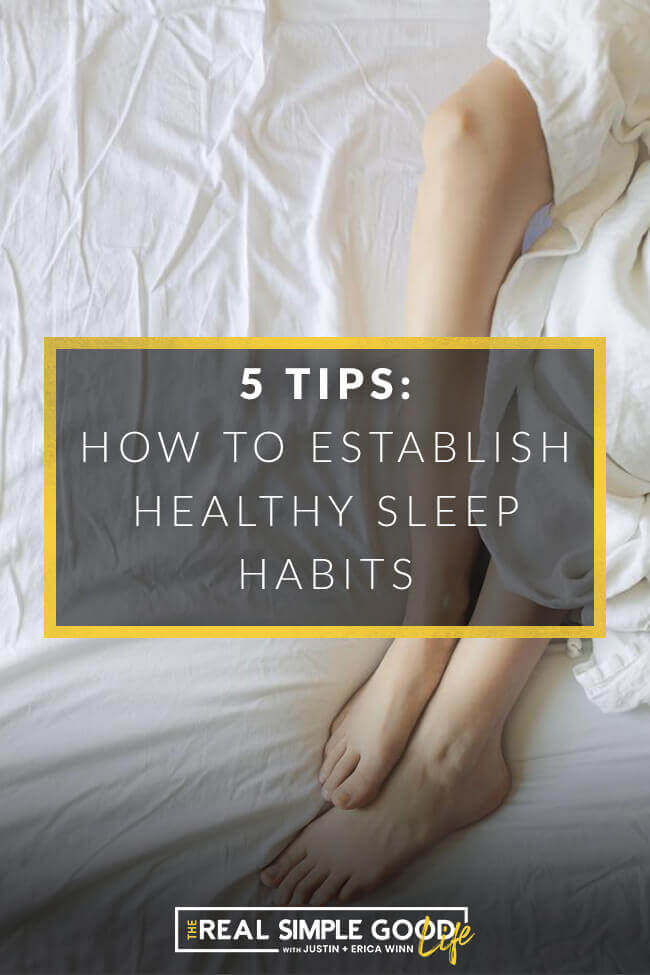 "Vertical image of someone's legs laying on bed partially covered by sheets with text overlay that says, ""5 Tips: how to establish healthy sleep habits + get better sleep naturally."""