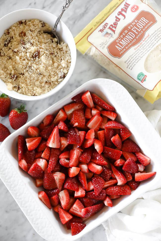 Vertical overhead image of strawberries in a baking dish with topping in a small bowl on the side and bob's red mill almond flour.